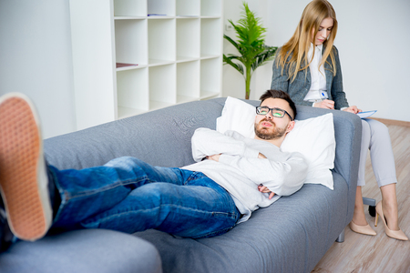 couple on couch: Young man on reception at psychologist Stock Photo