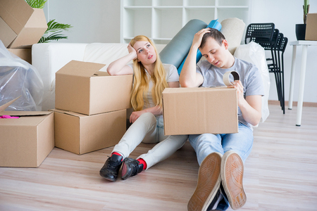 Tired couple with boxes Foto de archivo
