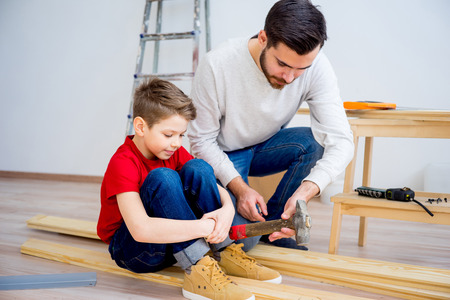 Father and son hammering nails