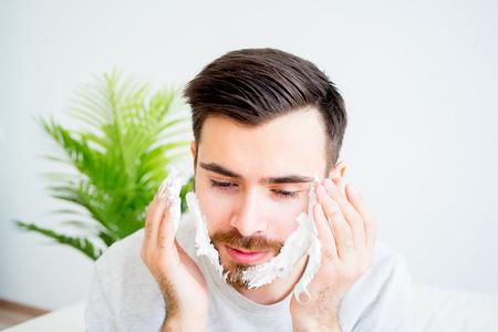 bathroom mirror: Man shaving his beard