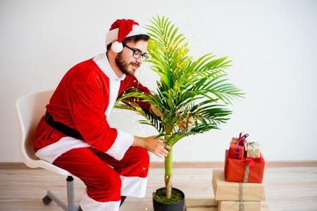 saint nicolas: Santa decorating a tree Stock Photo