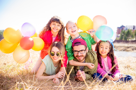 children party: Family lying on grass with balloons Stock Photo