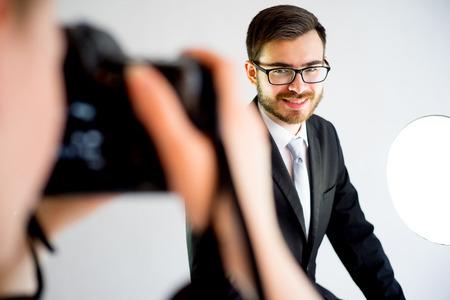 Weiblicher Fotograf, der Foto eines männlichen Modells im Studio macht Standard-Bild - 80929236