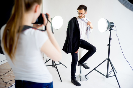 Female photographer taking picture of a male model in studio