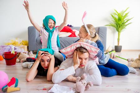 Tired parents and romping kids Reklamní fotografie