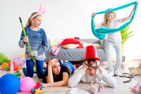 Tired parents and romping kids Stock Photo - 82274798
