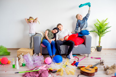 romp: Parents sleeping in a middle of a mess Stock Photo