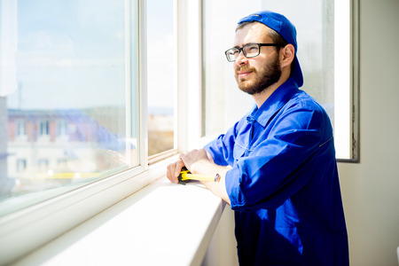 Construction worker installing window Stock Photo