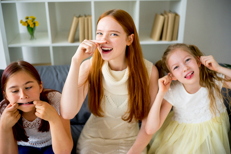 family tickle: Mother and two daughters making faces Stock Photo