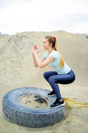 Girl exercising with a tyre Stock Photo