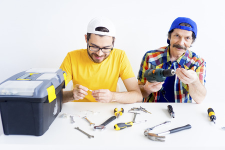 Father and son posing with workshop tools