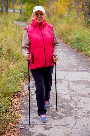 Senior dame nordic walking Stockfoto