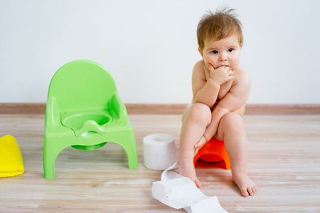 Baby sitting on a potty Stockfoto