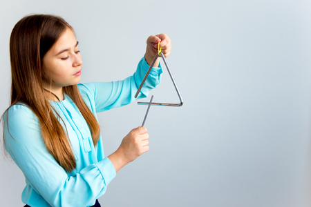 Girl plays a triangle