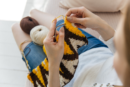 a woman knitting warm socks at home