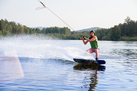 Young man riding wakeboard on a lake