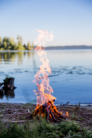 Beautiful campfire in the evening at lake. Fire burning in dusk at campsite