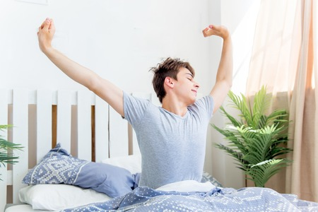 A young man waking up in bed in the morning Stock Photo