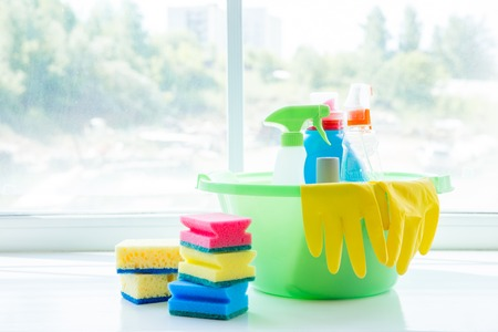 Bucket with cleaning supplies and tools on table Stock Photo