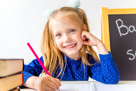 Glückliches niedliches fleißiges Kind sitzt an einem Schreibtisch drinnen