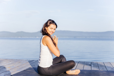 Young attractive smiling woman practicing yoga on a lake Banque d'images