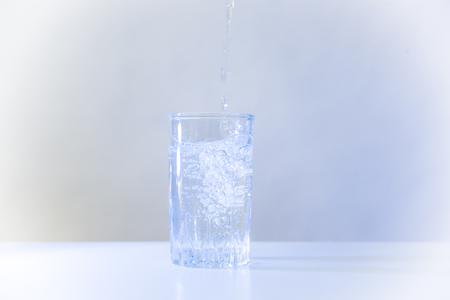 Glass of pure water on a white kitchen table