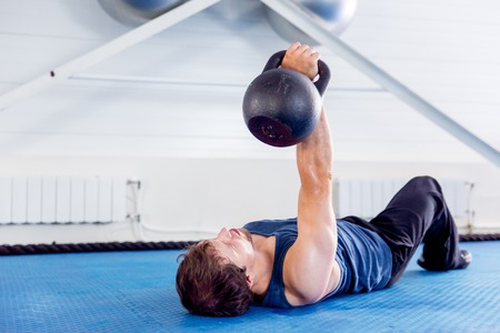 Young muscular man doing crossfit exercises in a gym