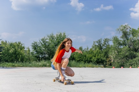 Beautiful skater woman riding on her longboard in the city