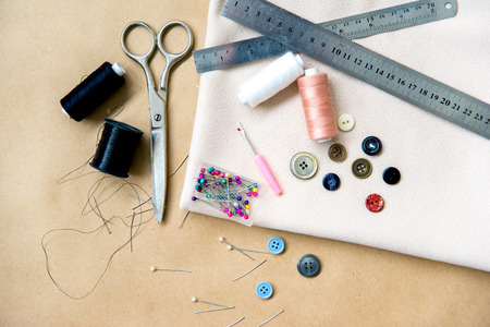 set of sewing tools - scissors, needles, buttons, thread on a table