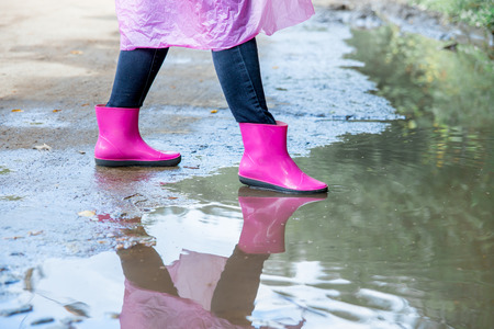 woman in rubber boots and a raincoat walking in the rain