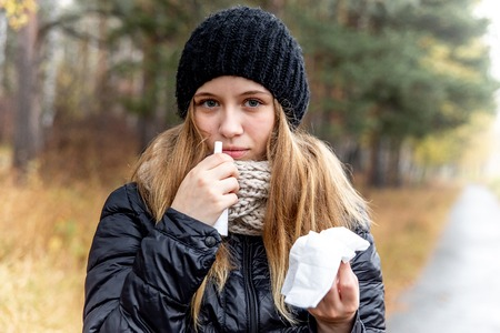 young woman with runny nose and using a nasal spray