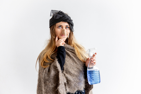 A young woman wearing a witch costume holding a washing liquid