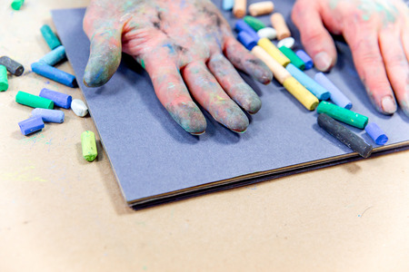 hands holding chalks and drawing on a blackboard