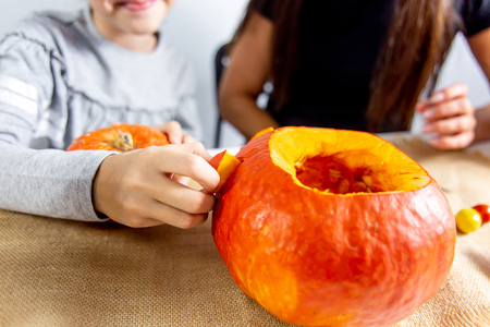 A mother and her daughter carving pumpkin together