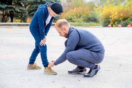 Father tying shoelace of son while playing in a park