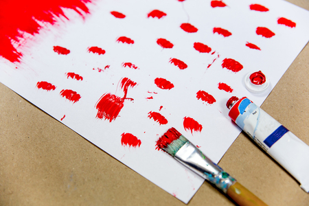 several paintbrushes with a painting on a table Stock Photo