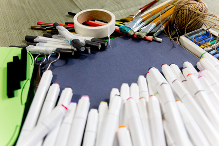work space on a table with pencils and paintbrushes Imagens
