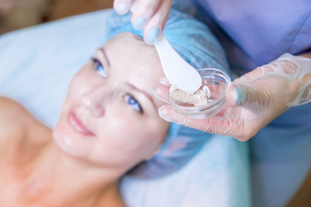 Young pretty woman enjoying a facial mask procedure Фото со стока