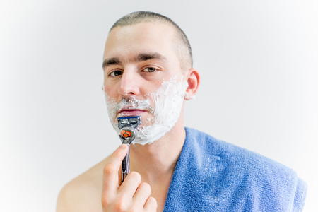 man is shaving his face in a bathroom