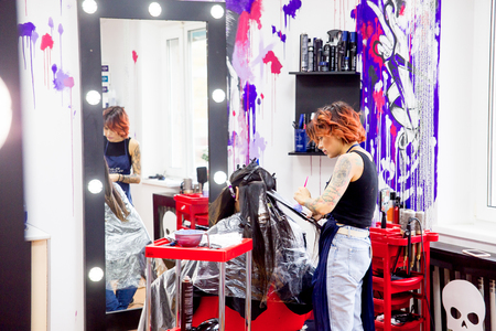 Professional hairdresser working with client in salon Фото со стока