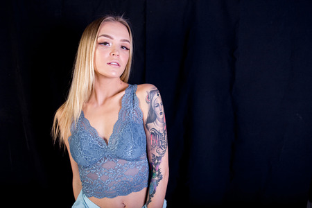 a studio shot of a young woman with tattoo