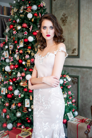 Beautiful young woman in an evening dress celebrating christmas