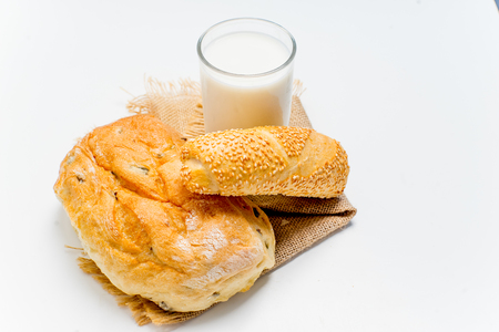 a glass of milk with bread and grains