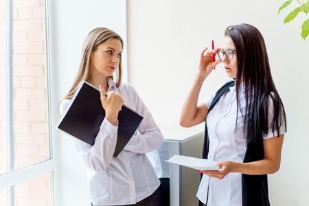 two businesswomen telling gossip in an office Фото со стока