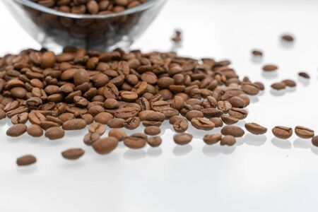 scattering of coffee beans on a glossy bright table with reflection.