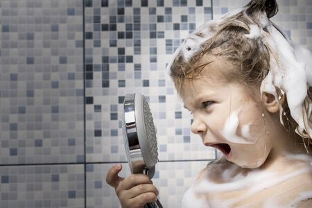 a little girl in foam is standing in the bathtub in her hand holding a shower, there is no water. the child cannot wash the soap, emotionally reacts