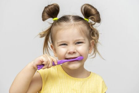 child in a yellow T-shirt with clean teeth brushing on a light background Banque d'images