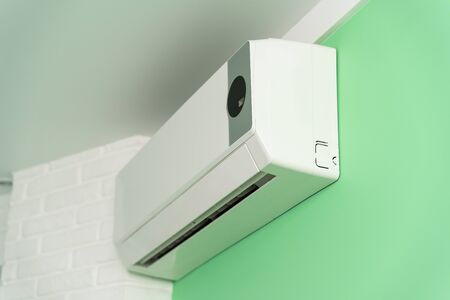 air conditioning on a green wall. cleaning, diagnostics and repair of air conditioning Фото со стока