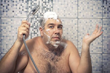 a 40-year-old man in a foam is standing in the bathtub holding a shower in his hand, water is not pouring, his hands are spread apart to the side in a sign of perplexity. water supply failure Banque d'images