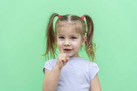 little girl 4 years old in a blue T-shirt on a green background in a blue T-shirt emotionally talks about something, index finger up